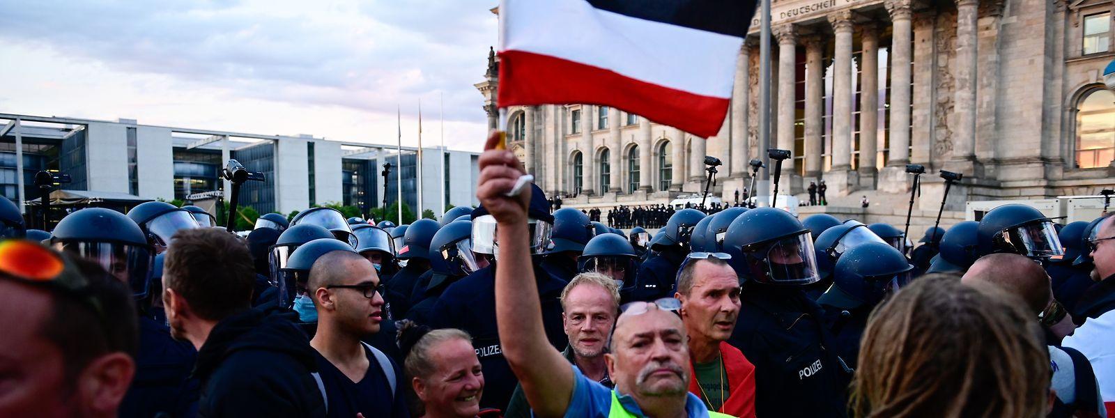 Teilnehmer einer Kundgebung gegen die Corona-Maßnahmen stehen vor dem Berliner Reichstag.