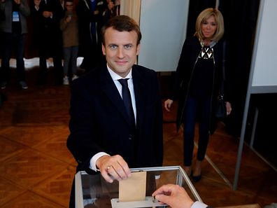 (FILES) This file photo taken on May 7, 2017 shows French presidential election candidate for the En Marche ! movement Emmanuel Macron casting his ballot next to his wife Brigitte Trogneux at a polling station in Le Touquet, northern France, during the second round of the French presidential election. Macron won a resounding victory in the French presidential election on May 7, 2015. Brigitte, 64,  has been a constant throughout his meteoric political rise. / AFP PHOTO / POOL / Philippe Wojazer