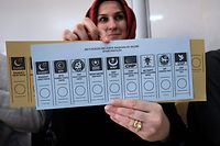 An election official holds up a voting ballot at a polling station during local elections in Istanbul on March 31, 2019. - Turkish voters go to the polls on March 31 for 30 major cities, 51 provincial municipalities and district councils. The vote will be a barometer on how well the AKP is faring after building its ballot box success on Turkey's growth. (Photo by Yasin AKGUL / AFP)