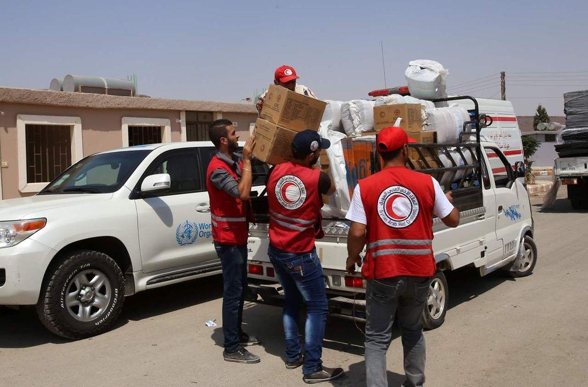 Mitarbeiter des Roten Halbmonds geben in Hrajela HIlfsmittel an die Flüchtlinge aus Daraja aus.