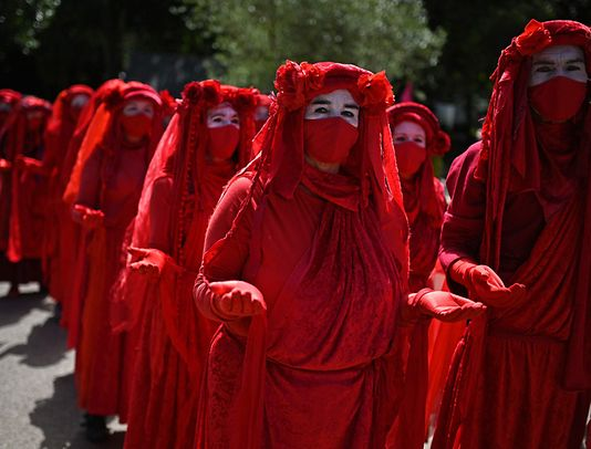Activists from the climate change protest group Extinction Rebellion, dressed in red robes and known as the 'Red Brigade' demonstrate in Falmouth, Cornwall during the G7 summit on June 12, 2021.
