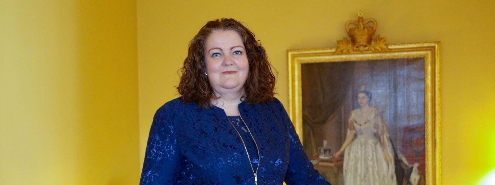 Die neue britische Botschafterin Fleur Thomas neben dem Porträt von Queen Elizabeth II.
