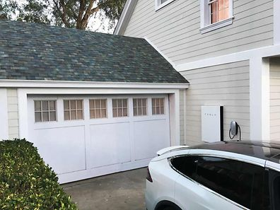 Ein ganz normales Haus, so scheint es. Doch es ist ein Energiesystem von Tesla: Die Dachschindeln sind kleine Solarzellen, die Batterie an der Wand speichert den erzeugten Strom und das Auto fährt damit.