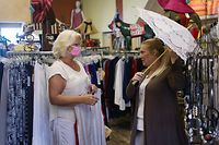 STUART, FLORIDA - MAY 04: Michelle Davis helps a shopper, wearing a protective mask, at the Island Cotton Company store, as the state of Florida enters phase one of the plan to reopen the state on May 04, 2020 in Stuart, Florida. Restaurants, retailers, beaches and some state parks reopen today with caveats, as the state continues to ease restrictions put in place to contain COVID-19. The counties of Palm Beach, Broward and Miami Dade continue to have their restrictions in place.   Joe Raedle/Getty Images/AFP == FOR NEWSPAPERS, INTERNET, TELCOS & TELEVISION USE ONLY ==