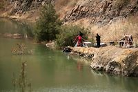 "Cyprus forensic police search a suspected dump site in Memi Lake in the village of Xyliantos, southwest of the capital Nicosia on April 26, 2019. - Cypriot authorities were combing lakes for the remains of three women and a girl dumped by a suspected serial killer, in a ""Good Friday"" hunt for bodies that has shocked the island. (Photo by Iakovos Hatzistavrou / AFP)"