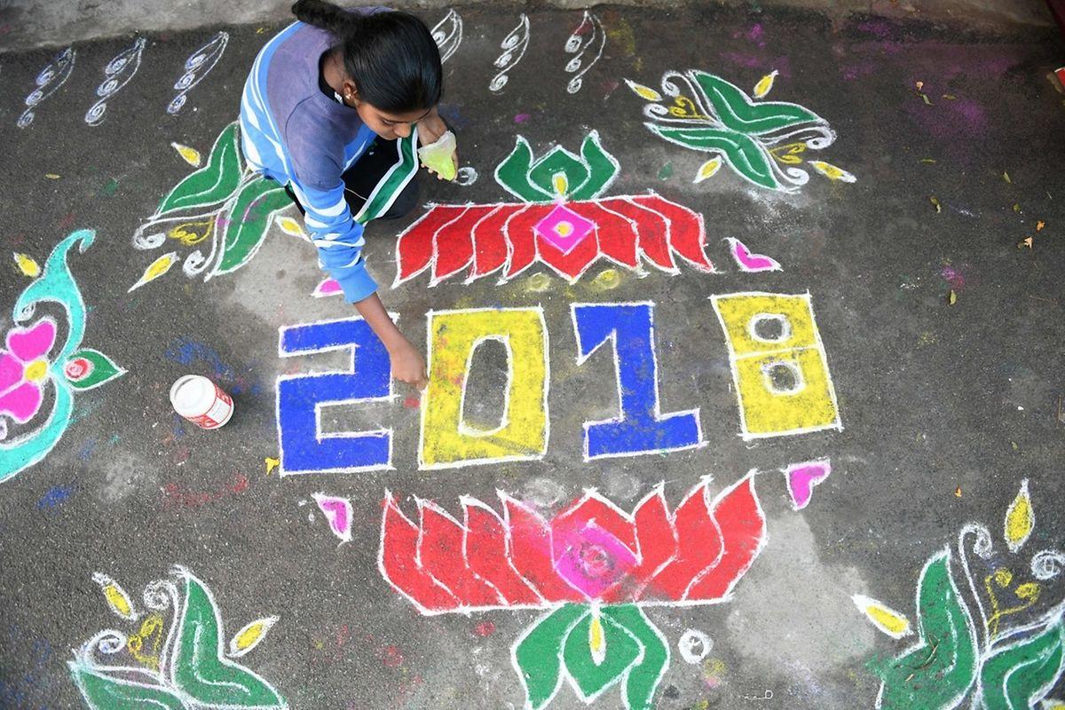 Une femme dessine un symbole porte-bonheur devant sa maison à Hyderabad en Inde