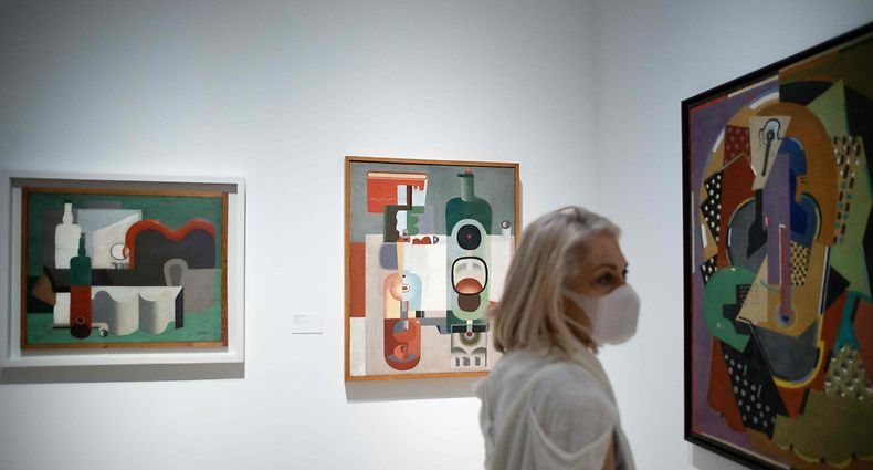 """A woman wearing a face mask visits the exhibition """"Genealogies of the art, or art history as visual art"""" at the Picasso Museum on May 27, 2020. - Many areas of the country that have already started to lift restrictions will now be able to take the next step, with the reopening of beaches, swimming pools, cinemas and museums. These reopenings are still accompanied by strict limits on the number of customers. (Photo by JORGE GUERRERO / AFP) / RESTRICTED TO EDITORIAL USE - TO ILLUSTRATE THE EVENT AS SPECIFIED IN THE CAPTION"""