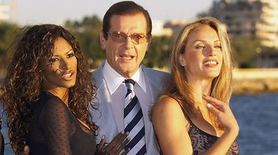 (FILES) This file photograph taken on October 5, 1999 shows  British actor Roger Moore (C) posing with actresses Traci Bingham (L) et Eva Halina in Cannes. British actor Roger Moore, who will forever be remembered for playing James Bond, died May 23, 2017, aged 89, his family announced in a statement on Twitter.  / AFP PHOTO / PASCAL GUYOT