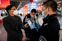 (FILES) This file photo taken on February 28, 2020 shows a passenger wearing a face mask as he shows a green QR code on his phone to show his health status to security upon arrival at Wenzhou railway station in Wenzhou. - To enter many offices, restaurants, parks or malls in China nowadays, people must show an app based on their travel history to determine if they're a coronavirus threat. (Photo by NOEL CELIS / AFP) / To go with AFP story China-Health-Virus-IT, FOCUS by Ludovic EHRET