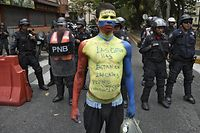 """A man with his body painted in the Venezuelan national flag's colors reading """"The stars are in the streets. We will soon be victorious Venezuela"""", demonstrates in front of riot police during an opposition demo near La Carlota Air Base in Caracas on May 4, 2019. - Venezuelan President Nicolas Maduro called on the armed forces to be """"ready"""" in the event of a US military offensive against the South American country, in a speech to troops on Saturday. His speech at a military base came as opposition leader Juan Guaido rallied his supporters in a new day of protests to press the armed forces to support his bid to dislodge Maduro. (Photo by YURI CORTEZ / AFP)"""
