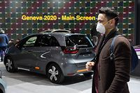 A man wearing a mask stand near a car on February 28, 2020 at the Geneva International Motor Show which has been cancelled due to the Covid-19 epidemic. - The Geneva International Motor Show, a major event on the auto industry calendar, has been cancelled after Switzerland banned large gatherings amid the new coronavirus epidemic, local authorities said on February 28, 2020. (Photo by Richard Juilliart / AFP)