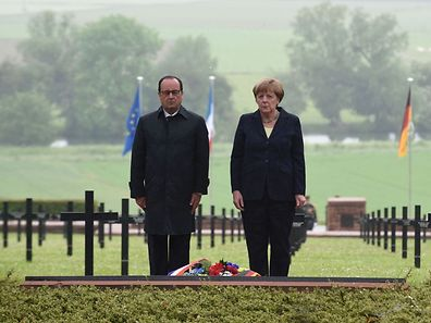 French President François Hollande (L) and German Chancellor Angela Merkel pay their respects after laying a wreath at a German cemetery in Consenvoye, northeastern France, on May 29, 2016, during a remembrance ceremony to mark the centenary of the battle of Verdun.