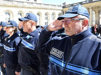 French municipal policemen observe a minute of silence on April 21, 2017 in the courtyard of the town hall in Bordeaux, southwestern France, to pay tribute to the police officer who was shot dead by an attacker on the Champs-Elysees the day before in Paris.  A handwritten note praising the Islamic State group was found near the attacker who shot dead a police officer and wounded two others on Paris's Champs Elysees, a source close to the probe said. / AFP PHOTO / MEHDI FEDOUACH