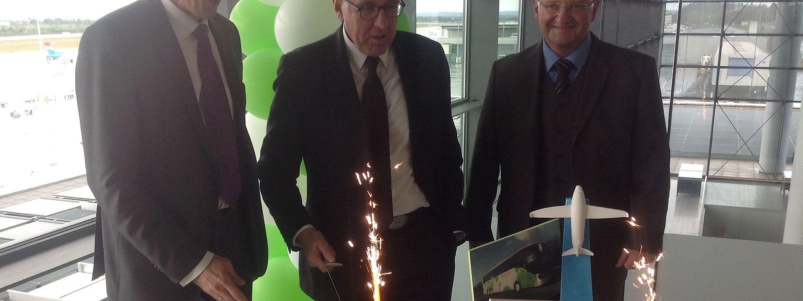 Le ministre des Transports, François Bausch, entouré par le directeur général de lux-Airport, Johan Vanneste et celui de Flibco, Wolfgang Schroeder, ont découpé le gâteau qui scelle leur travail commun