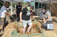 Für die unterste Putzschicht wird der Lehm mit gehäckseltem Stroh vermischt. Die Helfer scheuen sich nicht, dafür in eine improvisierte Wanne zu steigen.