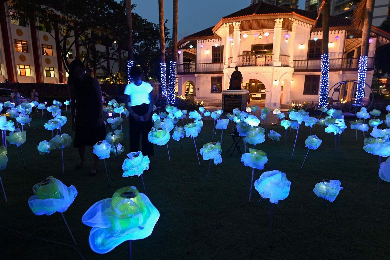 Singapur. Wenn der Tag die Nacht trifft: Die Mondblumen-Installation der Künstlerin Lee Yun Qin besteht aus 250 solar betriebene LED-Blumenskulpturen aus Draht – und ist vor der Sun Yat Sen Nanyang Memorial Hall zu sehen.