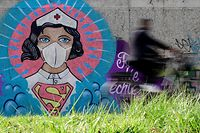A cyclist drives past a graffiti painted by artist Kai 'Uzey' Wohlgemuth featuring a nurse as Superwoman on a wall in Hamm, western Germany, on April 8, 2020 refering to the spread of the novel coronavirus COVID-19. (Photo by Ina FASSBENDER / AFP)