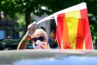 "A woman wearing a face mask waves Spanish flags during a ""caravan for Spain and its freedom"" protest by far-right party Vox against the Spanish government in Madrid on May 23, 2020. - Spain, one of the most affected countries in the world by the novel coronavirus with 28,628 fatalities, has extended until June 6 the state of emergency which significantly limits the freedom of movement to fight the epidemic. The left-wing government's management of the crisis has drawn a barrage of criticism from righ-wing parties who have denounced its ""brutal confinement"". (Photo by JAVIER SORIANO / AFP)"