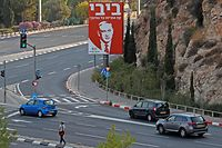 """An electoral billboard bearing a portrait of Israel's Prime Minister and Likud party chairman Benjamin Netanyahu hangs on a building in Jerusalem with a caption in Hebrew reading """"Bibi takes responsibility for education,"""" on September 16, 2019. (Photo by AHMAD GHARABLI / AFP)"""