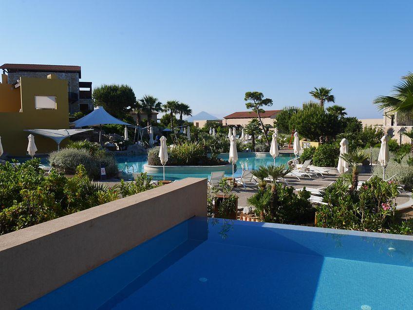 """Zum Abschlag bereit: Vor dem Clubhouse des """"Dunes Course"""" steht die Statue des Costa-Navarino-Gründers Vassilis C. Constantakopoulos (links). – Über einen eigenen kleinen Pool verfügen viele Zimmer im Erdgeschoss. – Moderne Kunst kommt ebenfalls im mehrfach ausgezeichneten Resort zu Ehren (rechts)."""