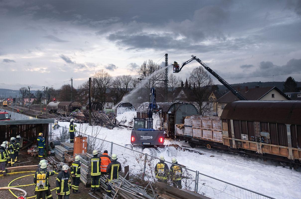 Ein Bagger des Technischen Hilfswerks beseitigt Trümmer nach dem Brand von Güterwaggons in Unkel am Rhein.