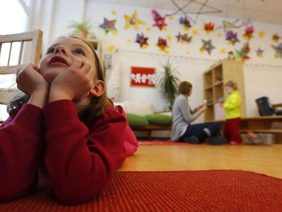 Children play with their nursery school teacher at their Kindergarten in Hanau, 30km (18 miles) south of Frankfurt, March 12, 2013. Despite a drive in German Chancellor Angela Merkel's first term to boost the number of childcare spots, Germany's birthrate remains one of the lowest in Europe.  REUTERS/Kai Pfaffenbach (GERMANY - Tags: POLITICS EDUCATION SOCIETY)