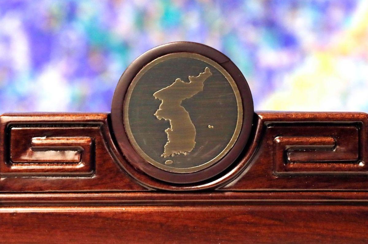 Nichts wird dem Zufall überlassen. Sogar die Dekoration hat Symbolcharakter. Auf jedem Stuhl befindet sich ein Medaillon, das die Umrisse der gesamten koreanischen Halbinsel zeigt. Inklusive umstrittene Inseln, auf die Japan einen Anspruch erhebt.
