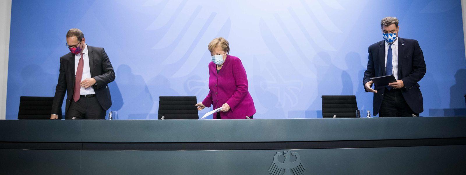 A chanceler Angela Merkel, o mayor de Berlim, Michael Mueller (à esquerda), e o presidente do Estado da Bavária, Markus Soeder, (à direita) na conferência de imprensa sobre a situação da crise sanitária no país, esta quarta-feira.
