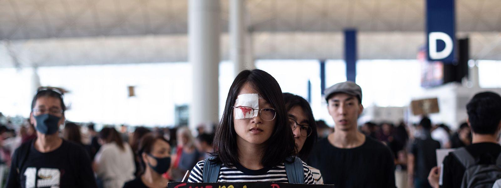 Auf dem Flughafen in Hongkong hält eine Demonstrantin eine Tafel mit den Forderungen ihrer Mitstreiter.