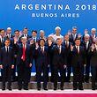 """30.11.2018, Argentinien, Buenos Aires: Teilnehmer des Gipfels haben sich im Tagungszentrum des G20 Gipfeltreffens in Buenos Aires zu einem Familienfoto aufgestellt, einige winken. Vom 30.11.-1.12.2018 findet in Buenos Aires der G20-Gipfel statt. Die """"Gruppe der 20"""" vereint die stärksten Industrienationen und aufstrebenden Volkswirtschaften. RECROP Foto: Ralf Hirschberger/dpa +++ dpa-Bildfunk +++"""