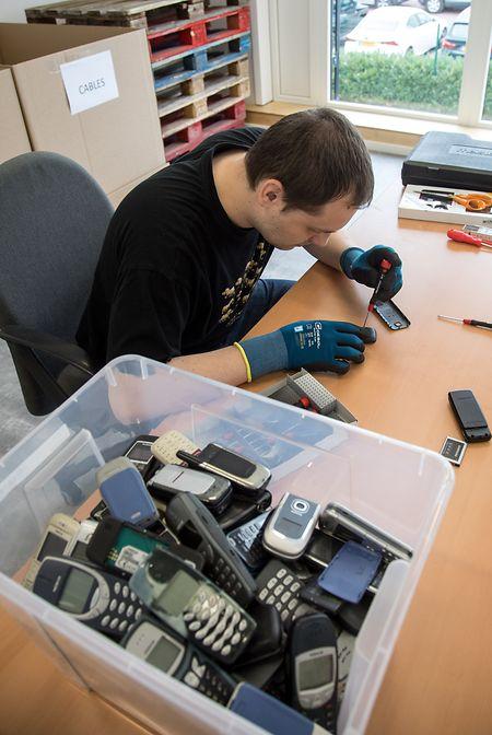 Per Hand werden die Mobiltelefone in ihre Einzelteile zerlegt.