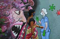 TOPSHOT - A pedestrian walks past a wall mural depicting a frontline medical staff stopping the Covid-19 coronavirus, in Navi Mumbai on June 7, 2021. (Photo by Indranil MUKHERJEE / AFP)