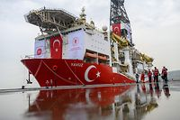 "(FILES) In this file photo taken on June 20, 2019 journalists walk next to the drilling ship 'Yavuz' scheduled to search for oil and gas off Cyprus, at the port of Dilovasi, outside Istanbul. - Turkey on July 10, 2019 vowed to continue drilling activities off Cyprus despite tensions with the European Union, which has called on Ankara to cease its ""illegal"" activities. The discovery of huge gas reserves in the eastern Mediterranean has sparked a dispute between EU member Cyprus and Turkey, which last month sent a second ship, the Yavuz, to search for oil and gas in the region. (Photo by BULENT KILIC / AFP)"