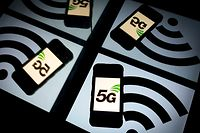 (FILES) In this file photo taken on February 16, 2019 this illustration picture shows the 5 G wireless technology logo displayed on a smartphone and a wireless signal sign displayed by a tablet in Paris. - Apple is expected on October 13, 2020, to unveil a keenly anticipated iPhone 12 line-up starring models tuned to super-fast new 5G telecom networks in an update considered vital to the company's fortunes. (Photo by Lionel BONAVENTURE / AFP)