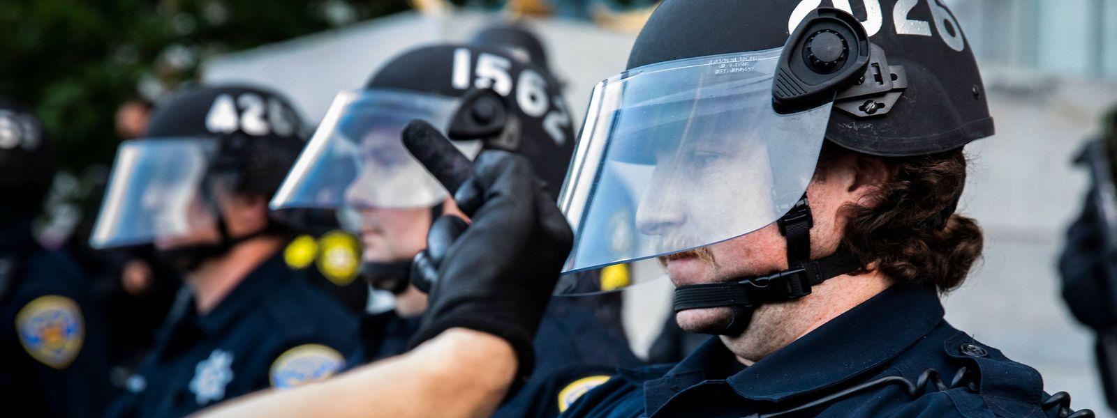 Ein Demonstrant zeigt einem Polizisten in San Francisco den Stinkefinger.