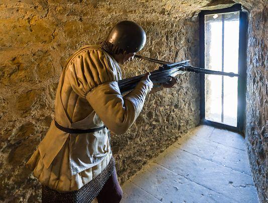A crossbowman takes aim from inside Sedan Castle Fort