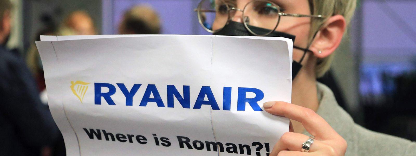 """Mulher com um cartaz que diz """"Onde está Roman (Protasevich)?!"""" na zona de chegadas do aeroporto de Vilnius, o destino inicial do voo da Ryanair. O avião da companhia low-cost foi forçado pelas autoridades biolerrussas a aterrar em Minsk para a detenção de um opositor ao regime de Lukashenko."""