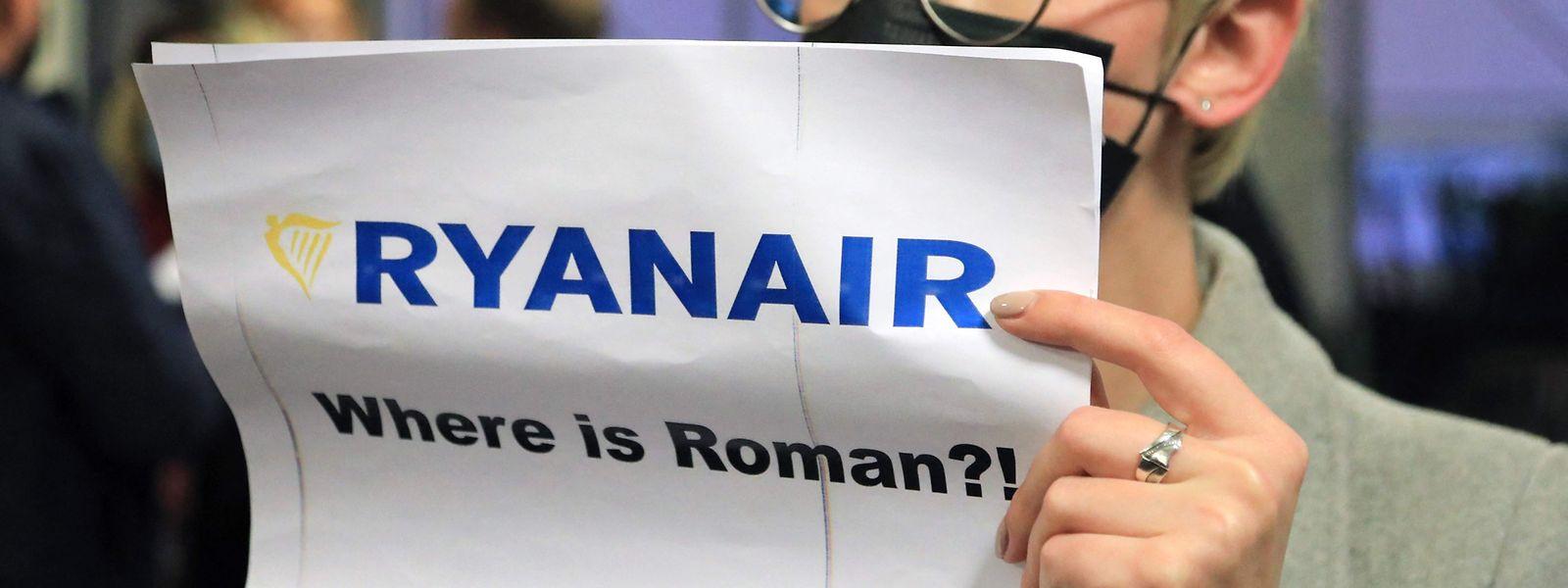 """Mulher com um cartaz que diz """"Onde está Roman (Protasevich)?!"""" na zona de chegadas do aeroporto de Vilnius, o destino inicial do voo da Ryanair que foi forçado pelas autoridades biolerrussas a aterrar em Minsk para a detenção de um opositor ao regime de Lukashenko."""