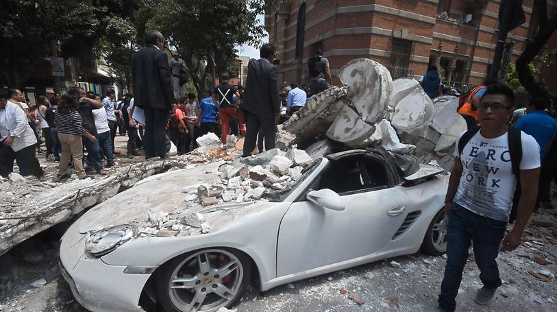A man stands next to a car crashed by debris from a damaged building after a quake rattled Mexico City on September 19, 2017. A powerful earthquake shook Mexico City on Tuesday, causing panic among the megalopolis' 20 million inhabitants on the 32nd anniversary of a devastating 1985 quake. The US Geological Survey put the quake's magnitude at 7.1 while Mexico's Seismological Institute said it measured 6.8 on its scale. The institute said the quake's epicenter was seven kilometers west of Chiautla de Tapia, in the neighboring state of Puebla.  / AFP PHOTO / Alfredo ESTRELLA