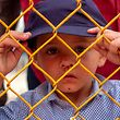 A Honduran migrant boy looks thorugh the fence of a warehouse used as shelter in Piedras Negras, Coahuila, Mexico, in teh border with the US on February 14, 2019. - Around 1,700 migrants traveling in caravan reached the US-Mexican border last week. (Photo by Julio Cesar AGUILAR / AFP)