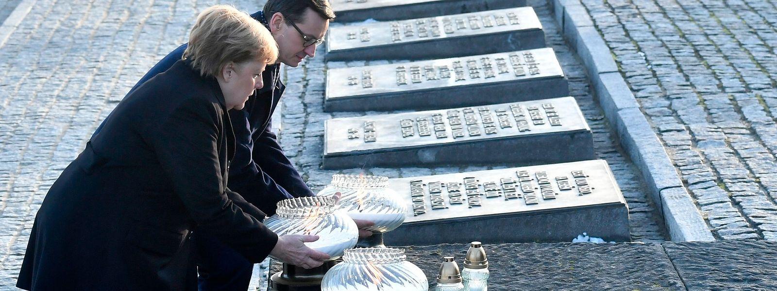 Die deutsche Bundeskanzlerin Angela Merkel und der polnische Premierminister Mateusz Morawiecki stellen Kerzen an das internationale Monument Auschwitz II-Birkenau.