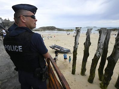 "French anti-riot policemen (CRS - compagnie Republicaine de Securite) patrol close to the beach of Saint-Malo, western France on July 21, 2016. French lawmakers voted massively on July 20, 2016, to extend a state of emergency as President Francois Hollande said that a call to boost reserve forces had paved the way towards a ""National Guard."" The government is scrambling to find new ways to assure a jittery population after its third major attack in 18 months saw a truck driver plough into a crowd celebrating Bastille Day in Nice, killing 84 people.  / AFP PHOTO / DAMIEN MEYER"