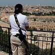 A Jewish man holding a gun stands on the Mount of Olives looking out over Jerusalem's Old City and the Dome of the Rock (C) as he observes two minutes of silence to mark Remembrance Day which commemorates Israel's fallen soldiers on April 18, 2018. Israel mark the Remembrance to commemorate over 23,646 fallen soldiers since 1860, just before the celebrations of the 70th anniversary of its creation according to the Jewish calendar. / AFP PHOTO / AHMAD GHARABLI