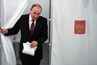 Presidential candidate, President Vladimir Putin walks out of a voting booth at a polling station during Russia's presidential election in Moscow on March 18, 2018. / AFP PHOTO / POOL / Yuri KADOBNOV