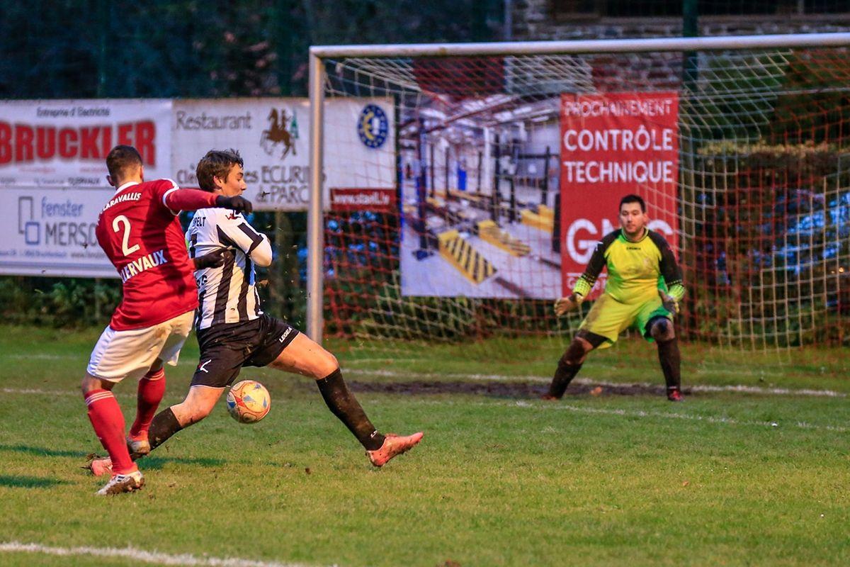 Le défenseur de Wilwerwiltz, Gilles Schmitz (en noir et blanc) tente par tous les moyens d'enrayer la percée de Nelson Fernando da Silva (en rouge, n°2)