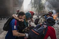 A demonstrator in distress is helped by others at Plaza Italia during the fifth straight day of protest which erupted over a now suspended hike in metro ticket prices, in Santiago, on October 22, 2019. - President Sebastian Pinera convened a meeting with leaders of Chile's political parties on Tuesday in the hope of finding a way to end street violence that has claimed 15 lives, as anti-government campaigners threatened new protests. (Photo by Pedro Ugarte / AFP)