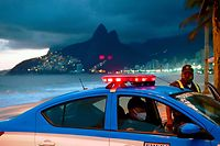 "Police wearing facemasks as a measure against the spread of the new coronavirus are seen with their car on Ipanema beach in Rio de Janeiro, Brazil, on May 19, 2020. - Amid the pandemic, police operations in the ""war"" on drug trafficking continue to claim lives and frequently interrupt humanitarian work by community leaders, such as the distribution of food, hygiene products and prevention campaigns. In April 2020 alone, the Rio de Janeiro state police killed 177 people, 43% more than in April 2019, a record year in terms of deaths by state agents: 1,810. (Photo by CARL DE SOUZA / AFP)"