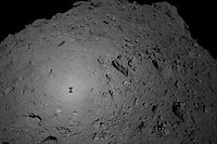 """(FILES) This handout file photograph received from the Hayabusa2 spacecraft and made available by the Japan Aerospace Exploration Agency (JAXA) on October 3, 2018 shows the shadow of the Japanese spacecraft Hayabusa2 (L) over the asteroid Ryugu during the French-German Mobile Asteroid Surface Scout (MASCOT) deployment operation. - The Hayabusa2 probe is expected to land on a distant asteroid on February 22, 2019, aiming to blast a """"bullet"""" into the surface to collect clues about the origins of Earth and the solar system. (Photo by Handout / JAXA / AFP) / --- RESTRICTED TO EDITORIAL USE - MANDATORY CREDIT """"AFP PHOTO / JAXA / FILES"""" - NO MARKETING NO ADVERTISING CAMPAIGNS - DISTRIBUTED AS A SERVICE TO CLIENTS ---"""