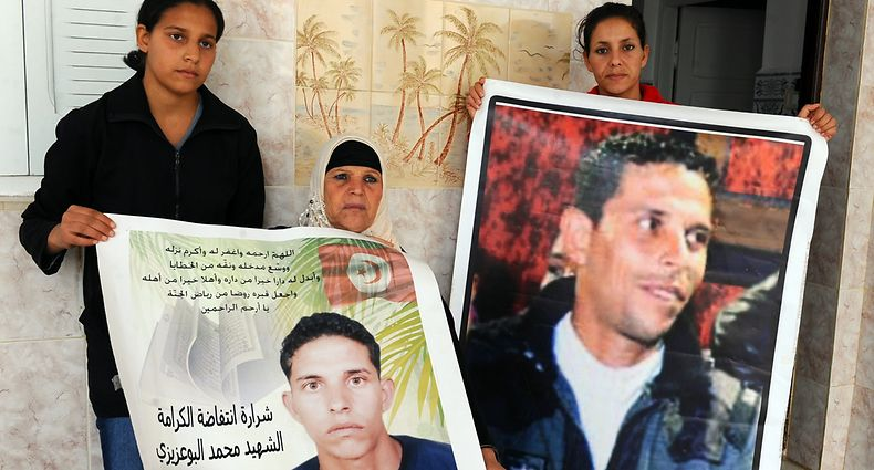 "(FIELS) A picture taken on November 15, 2011 shows the mother of Mohamed Bouazizi, the fruitseller whose self-immolation sparked the revolution that ousted a dictator in Yunisia and ignited the Arab Spring, Manoubia Bouazizi (C) and her daughters Leila (R) and Basma (L) posing posing with posters of Mohamed, in Tunis. Slogan reads: ""The spark of the revolution -- martyr Mohamed Bouazizi."" Bouazizi, a 26-year-old university graduate who has only been able to find work as a fruitseller, sets himself alight on December 17, 2010 to protest harassment and unemployment. Two days later rioting breaks out. Bouazizi dies from his burns on January 5, 2011. During the unrest some 300 people are killed, according to the UN, and hundreds are arrested.     AFP PHOTO/ FETHI BELAID"