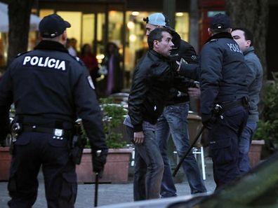 Agentes da PSP tentam acalmar um adepto portista, enquanto adeptos do Benfica festejam a conquista do titulo de Campeão da Primeira Liga de Futebol, no Porto, 9 de maio de 2010. JOSE COELHO/LUSA
